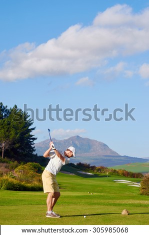 golfer hitting driver off tee box on a beautiful scenic course - stock photo
