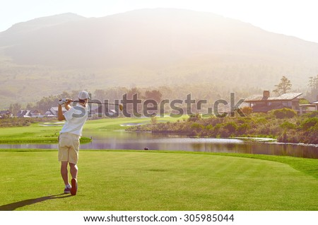 golfer hitting golf shot with club on summer vacation - stock photo