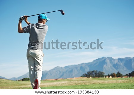 Golfer hitting tee shot with driver from teebox, on beautiful course and good strike - stock photo