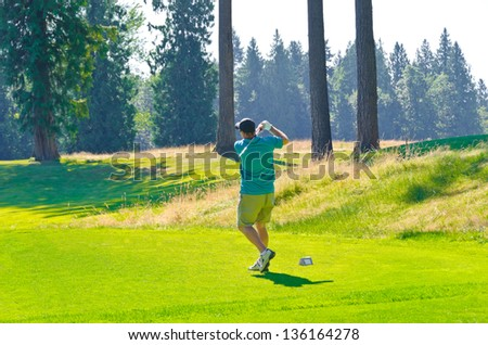 Golfer hitting the ball at the beautiful golf course. - stock photo
