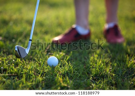 Golfer hitting the ball stick up close