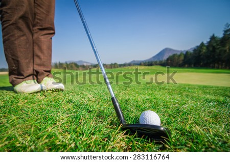Golfer is chipping a golf ball onto the green with driver golf club. Legs and feet in the background. Green grass with forrest and mountains in the background. Soft focus or shallow depth of field.  - stock photo