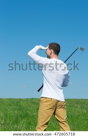 golfer looking away defensively from the sun hand