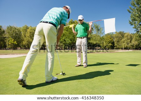 Golfer making final putt, caddy holding a flag