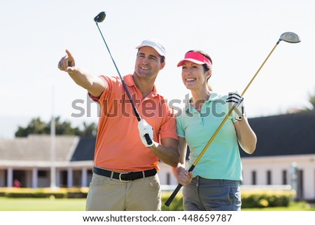 Golfer man pointing while standing by woman on field