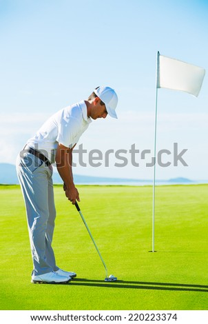 Golfer on Putting Green Hitting Golf Ball into the Hole - stock photo