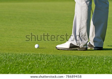 Golfer on the course at the hole - stock photo