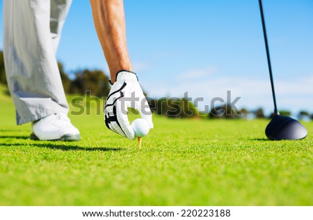 Golfer Placing Golf Ball on the Tee - stock photo