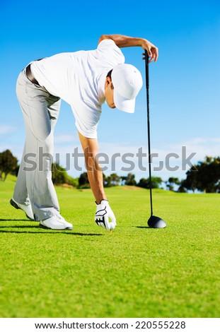 Golfer Placing Golf Ball on the Tee - stock photo