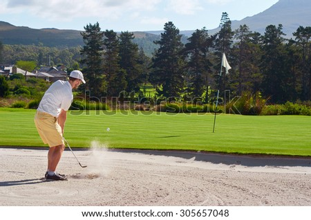 golfer playing a sand shot from bunker hazard - stock photo
