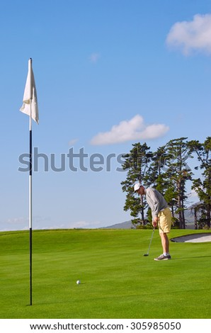 golfer playing on beautiful scenic course on summer vacation - stock photo