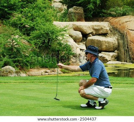 Golfer preparing for the putt on the green. - stock photo