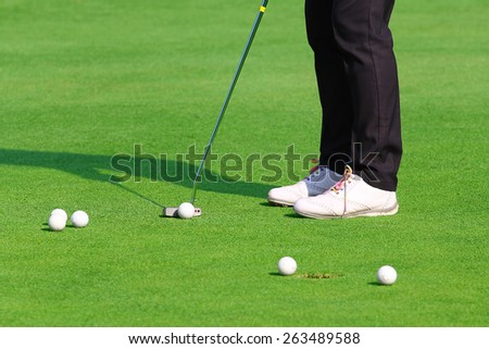 golfer putting a golf ball in to hole. - stock photo