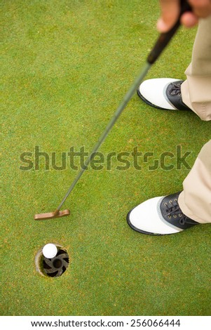 Golfer putting golf ball in the hole at golf course - stock photo