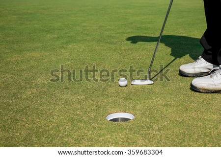 Golfer putting golf ball under sunshine - stock photo
