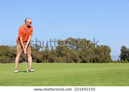 Golfer putting golf shot with club on course while on vacation  - stock photo