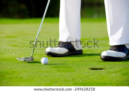 Golfer putting on green, detail - stock photo