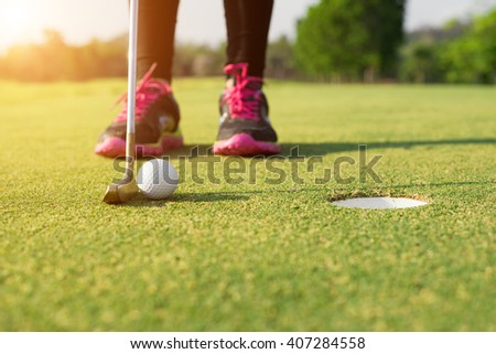 Golfer putting on green for birdie while on vacation - stock photo