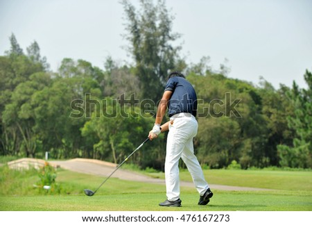 Golfer putting on the green, golf ball in motion.