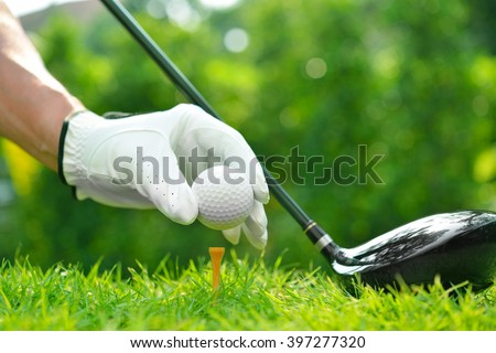 Golfer's hand holding golf ball with driver on green grass with golf course background - stock photo