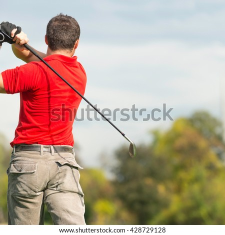 Golfer's swing from back, selective focus, shallow depth of field - stock photo
