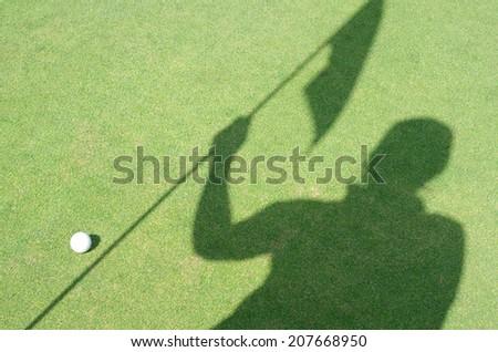 Golfer shadow hold flag on green golf - stock photo