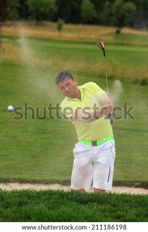 golfer swing at the ball from sand  - stock photo