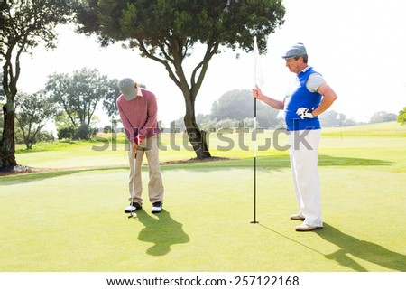 Golfer swinging his club with friend at the golf course - stock photo