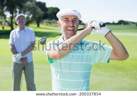 Golfer swinging his club with friend behind him on a sunny day at the golf course - stock photo