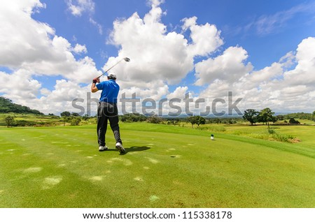 Golfer swinging his gear and hit the golf ball from tee to the fairway, slow shutter motion blur - stock photo