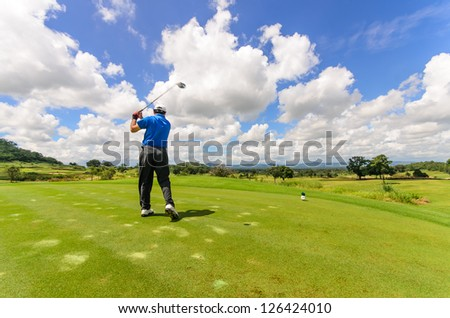 Golfer swinging his gear and hit the golf ball from tee to the fairway, slow shutter motion blur
