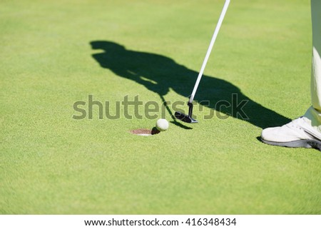 Golfer taps the ball in from few inches away. - stock photo