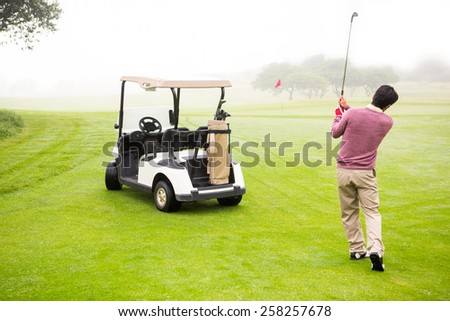 Golfer teeing off next to his golf buggy at the golf course - stock photo
