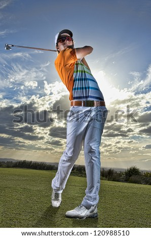 Golfer tees off in late afternoon light - stock photo