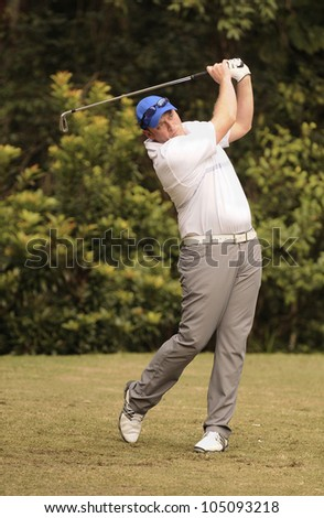 Golfer tees off with a iron - stock photo