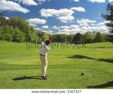 Golfer tees off with a long drive - stock photo