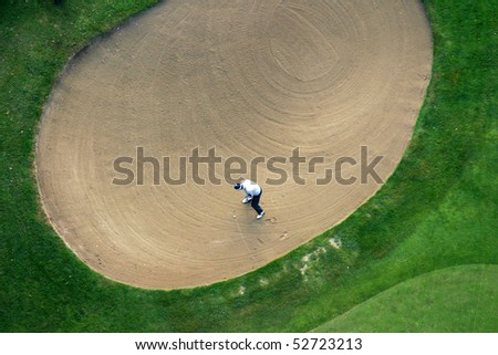 Golfer trying to put the ball out of the sand - stock photo