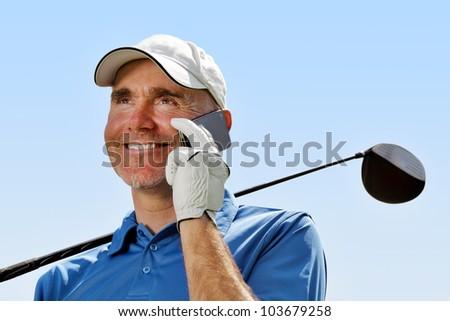 Golfer using mobile phone - stock photo