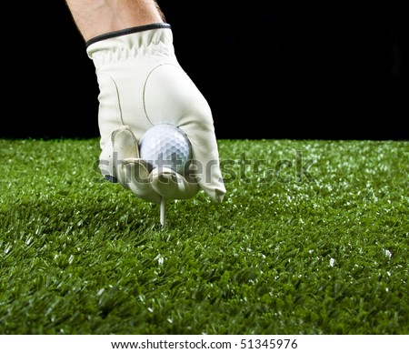 golfer wearing a golf glove putting a ball and a tee in the ground before teeing off, copy space. - stock photo