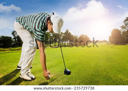 Golfers are a golf ball on a field in summer - stock photo