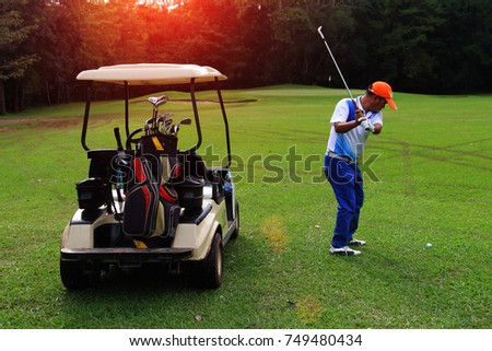 Golfers are playing golf carts on an evening golf course in thailand