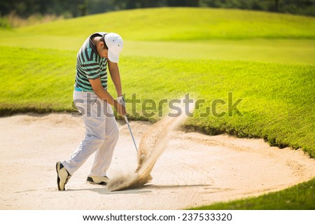 Golfers hit the ball in the sand. Speed and Strength - stock photo