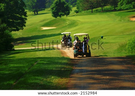 Golfers ride in a cart along a trail on the course - stock photo