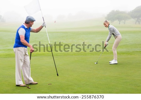 Golfing couple on the golf course on a foggy day - stock photo