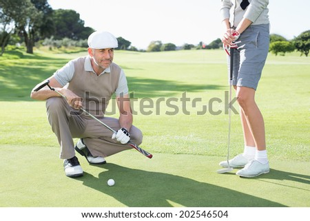 Golfing couple on the putting green on a sunny day at the golf course