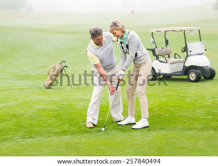 Golfing couple putting ball together on a foggy day at the golf course - stock photo