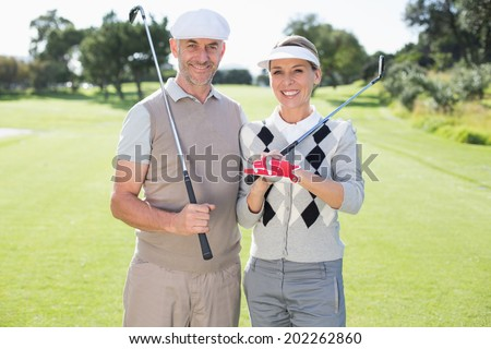 Golfing couple smiling at camera holding clubs on a sunny day at the golf course - stock photo