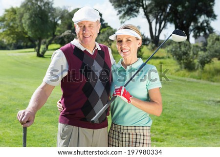 Golfing couple smiling at camera on a sunny day at the golf course - stock photo