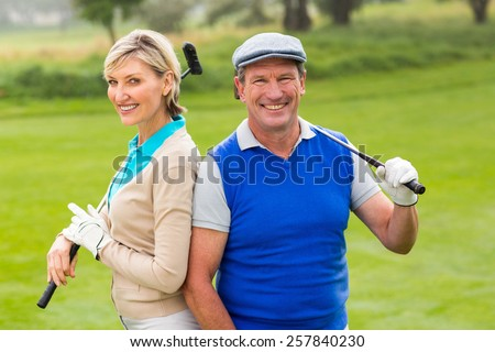 Golfing couple smiling at camera on the putting green on a sunny day at the golf course - stock photo