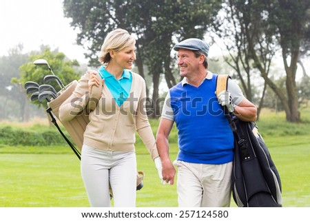 Golfing couple smiling at each other on the putting green on a sunny day at the golf course - stock photo